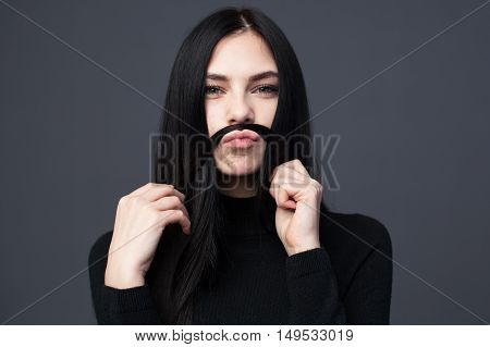 Young brunette woman making mustache from her hair gray background