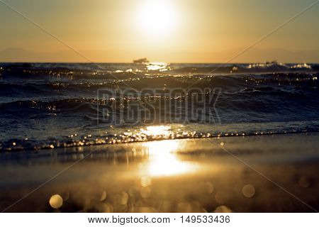 Sunset on the coast with waves and bokeh.