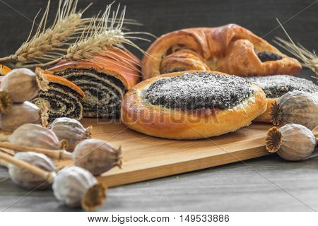 poppy seed cake and strudel on a wooden board with poppy heads in the foreground.