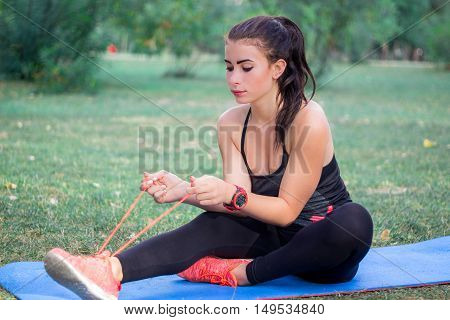 Young fitness girl ties bootlaces for training workout outdoor