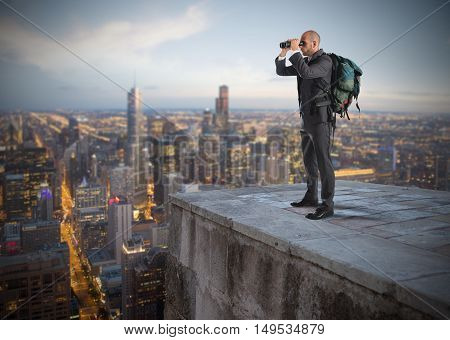 Businessman with backpack and binoculars watching from above the city