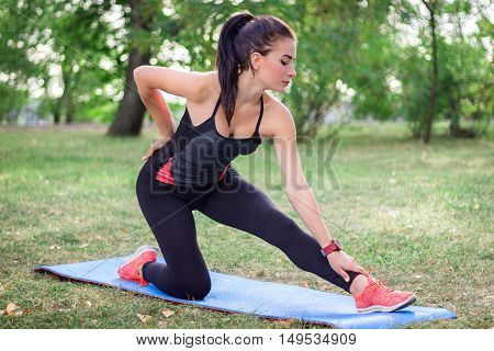 Young fitness girl stretches during training workout outdoor