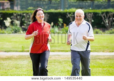 Smiling Senior Couple Running Together In Park
