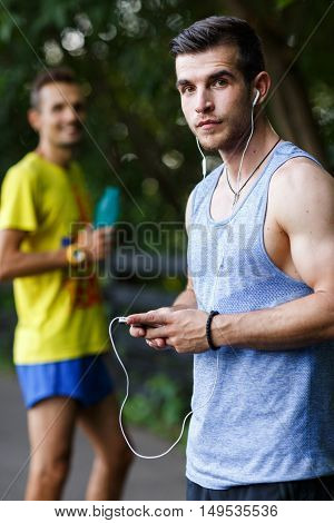 Two young sportsman in park relaxing after workout in summer