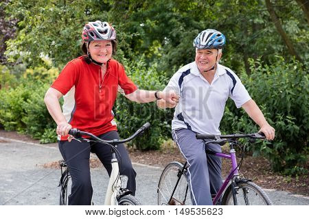 Smiling Senior Couple Holding Hands While Riding Bicycle In Park
