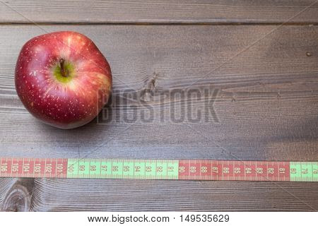 Red Apple With Measuring Tape On Wooden Table