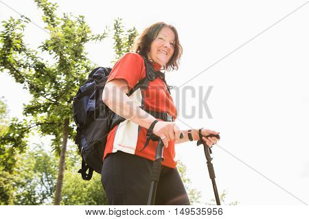 Portrait Of A Happy Senior Female Hiker With Hiking Pole