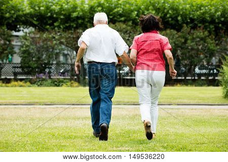 Rear View Of Senior Couple Running Together In Park