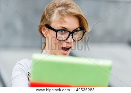 Portrait of surprised girl with tablet in their hands closeup