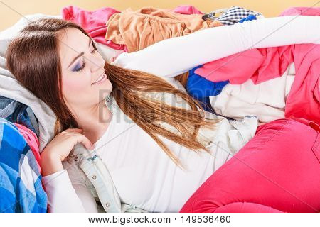 Happy Woman Lying On Clothes. Mess And Disorder.