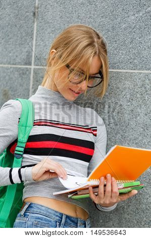 Young girl looks at open book standing at Gray wall