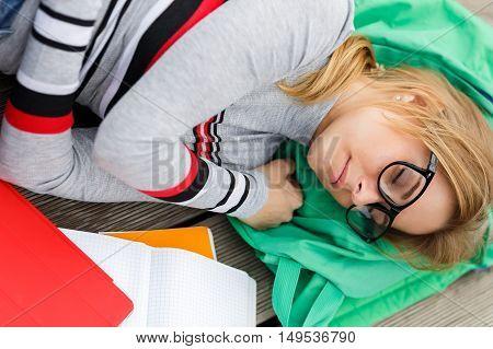 Blonde sleeping on backpack at wooden floor