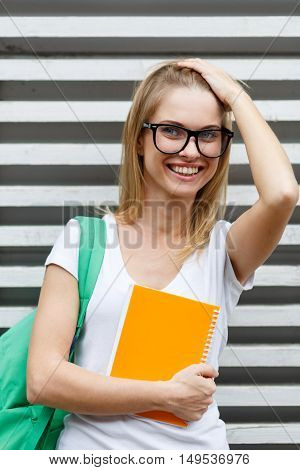 Laughing girl straightens hair with backpack on shoulder against backdrop of wooden fence