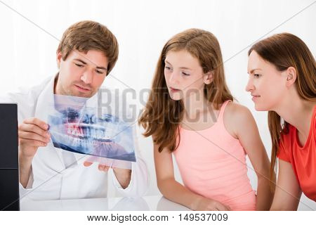 Young Male Doctor Showing Teeth Xray To Mother And Daughter In Clinic