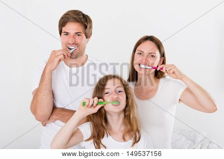 Parent With Their Daughter Brushing Teeth Together