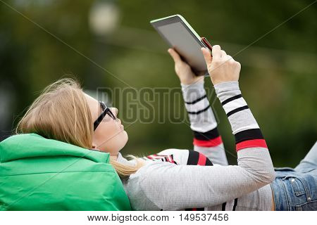 young girl looks at Tablet lying his head on backpack