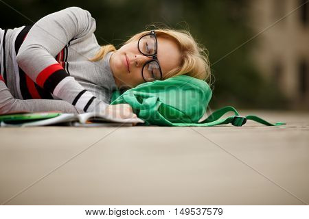 sleeping girl with open book and Tablet PC on wooden stage