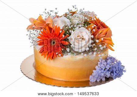 Orange cake, decorated with fresh flowers. On a white background.