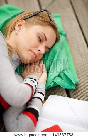 sleeping girl spectacled with books outdoors, close-up
