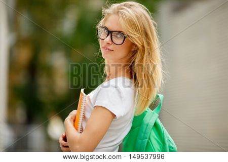 Student in glasses with backpack on shoulder standing on street