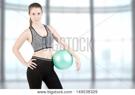Fit Woman Standing Holding A Pilates Ball