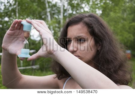 The girl was staring at an hourglass