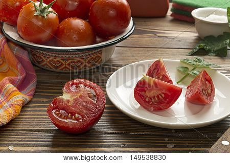 Fresh ripe tomatoes in yellow bowl half of cutted tomato
