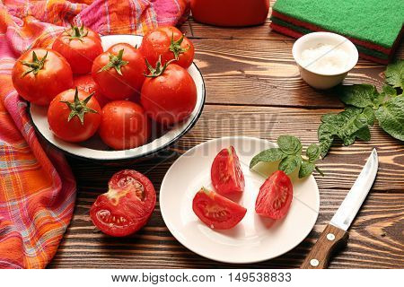Fresh ripe tomatoes in bowl half of cutted tomato and chopped tomatoes on white souser