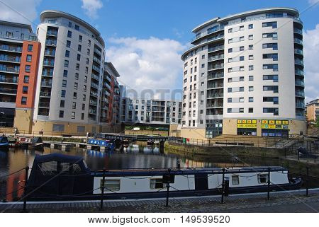 Leeds, United Kingdom - June 23, 2014. Waterfront apartment complexes along Armouries Way in Leeds, with River Aire, boats and people.