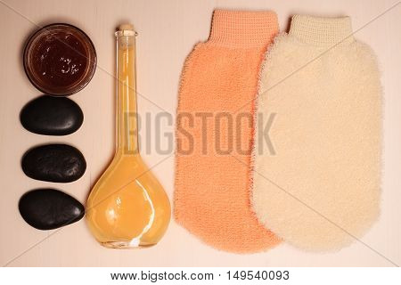 Beauty treatment and body care. Spa products bath accessories wisp massage glove and soap on wooden board top view.
