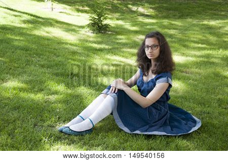 The girl in glasses sits on the lawn