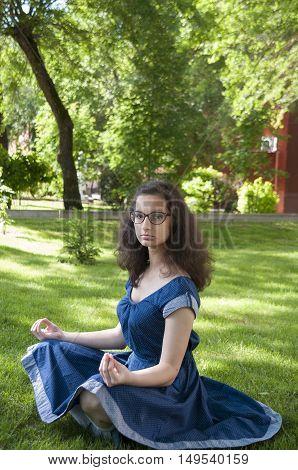 Portrait of meditating girl in a park in blue dress