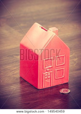 Finance mortgage housing real estate savings concept. House like cash box. Piggy bank in home shape with coin.