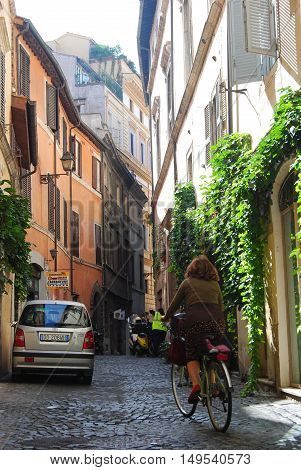 Rome, Italy - October 9, 2014. Street view on Vicolo Savollo street in Rome city center, with residential buildings, people and cars.