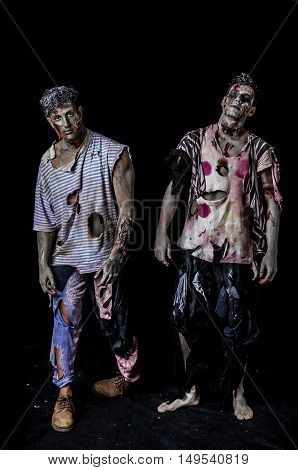 Two male zombies standing on black background walking towards camera