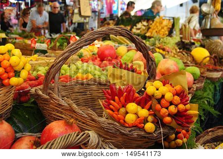 Rome, Italy - October 10, 2014. Campo de' Fiori market in Rome, with straw baskets, fruits, vegetables and people in the background.