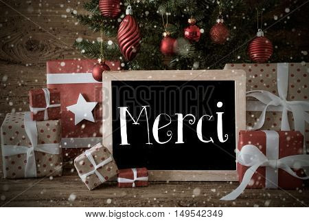 Nostalgic Christmas Card For Seasons Greetings. Christmas Tree With Balls And Snowflakes. Gifts Or Presents In The Front Of Wooden Background. Chalkboard With French Text Merci Means Thank You