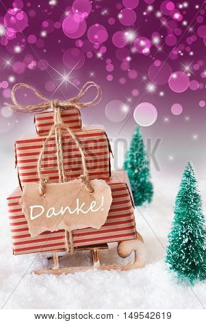 Vertical Image Of Sleigh Or Sled With Christmas Gifts Or Presents. Snowy Scenery With Snow And Trees. Purple Sparkling Background With Bokeh. Label With German Text Danke Means Thank You