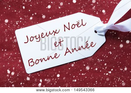 One White Label On A Red Textured Background. Tag With Ribbon And Snowflakes. French Text Joyeux Noel Et Bonne Annee Means Merry Chistmas And Happy New Year