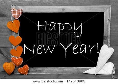 Chalkboard With English Text Happy New Year. Orange Hearts. Wooden Background With Vintage, Rustic Or Retro Style. Black And White Image With Colored Hot Spots.