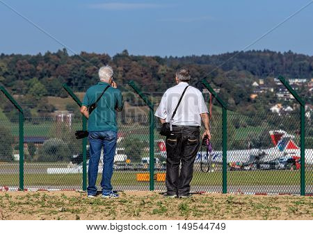 Kloten, Switzerland - 29 September, 2016: two men observing the Zurich Airport. The Zurich Airport, also known as the Kloten Airport, is the largest international airport of Switzerland and the principal hub of Swiss International Air Lines.