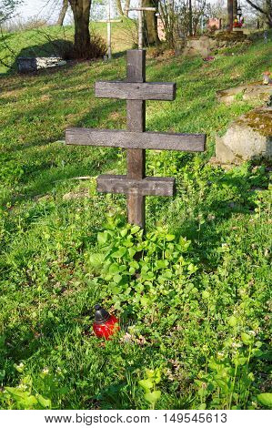 wooden anonymous cross and red candle on the old graveyard