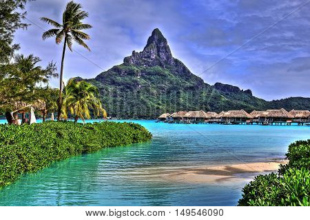 View on Mount Otemanu through turquoise lagoon palms and overwater bungalows on the tropical island Bora Bora honeymoon destination near Tahiti French Polynesia Pacific ocean. HDR picture.