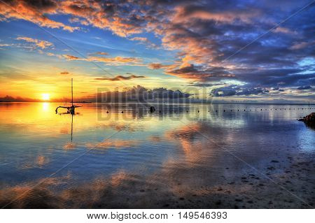 Amazing colorful sunset on the beach of Moorea French Polynesia. HDR (High dynamic range) picture.
