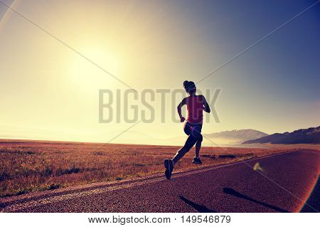 young fitness woman runner athlete running at sunrise road