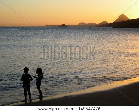 Silhouette of two children at sunset on a beautiful beach in Brazil.