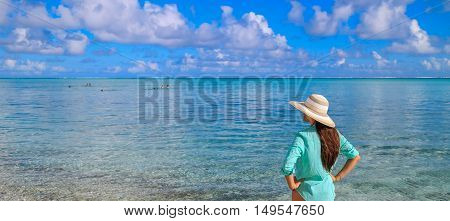 Outdoor summer portrait of young pretty woman looking to the ocean at tropical beach enjoy her freedom and fresh air wearing stylish hat and clothes.