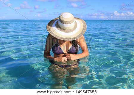 Girl on a tropical beach with hat.