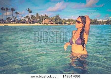 Attractive young caucasian long hair woman in purple swimsuit on the beach.Retro style color tones.