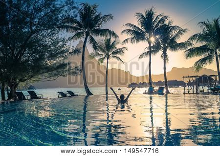 Silhouette of a girl in the pool. Sunset in Bora Bora French Polynesia . Mount Otemanu in the background. Retro style color tones.
